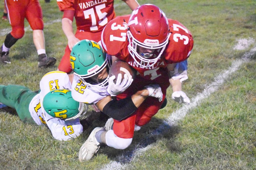 John Broux photos Vandalia Vandal Preston Nestrick gets tackled on a big gain in the first quarter en route to a 42-6 thumping of the Piasa Birds Friday night at Mark Greer Field here. The win was revenge for a loss suffered at the hands of the Birds last spring in a game played at Piassa.