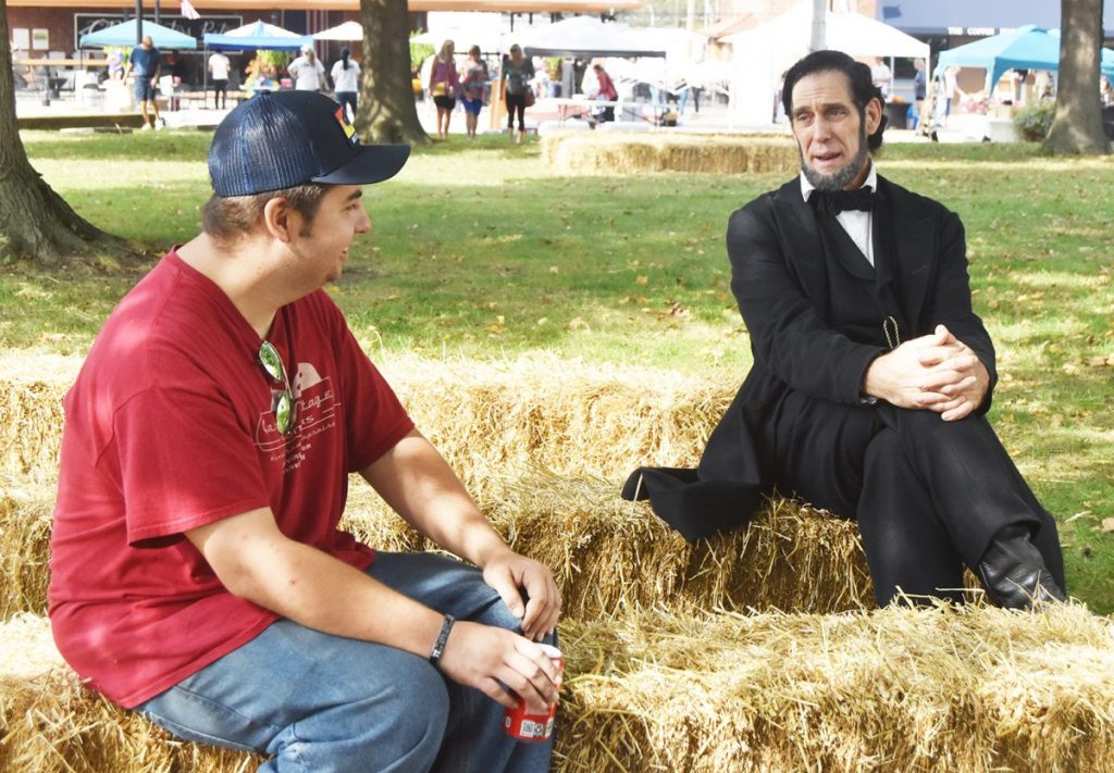 Mike Warren, of Vandalia, takes a break at the Grand Levee to sit and chat a spell will Abe, as portrayed by Springfield's Randy Duncan. Duncan told Warren, about the time he (Lincoln) paradoned the White House turkey, the first such president to do so. Other photos from the event appear in today's newspaper.